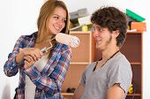 stock photo of she-male  - Couple renovating together as she holds up a roller with pink paint in front of his face - JPG
