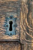 picture of keyhole  - Keyhole with metal plate in a wooden door - JPG