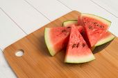 stock photo of watermelon slices  - Closeup of watermelon slices on wooden vintage background - JPG