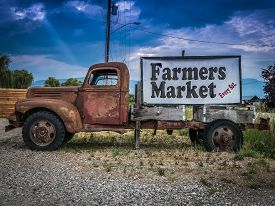 stock photo of food truck  - Sign For A Farmers Market On The Side Of A Vintage Rusty Truck - JPG