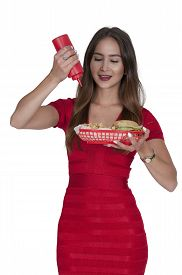 image of squirt  - Woman squeezing a ketchup squirt condiment bottle on a bun - JPG