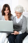Elderly woman with grandaughter with laptop computer