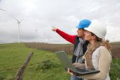 stock photo of wind energy  - Engineers working by wind turbines field - JPG
