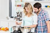 Smiling young couple cooking food in the kitchen poster