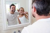 Father and daughter brushing their teeth in the bathroom poster