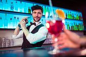 Portrait of confident handsome barkeeper preparing cocktail at bar counter poster
