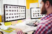 Cropped image of young male editor working on photographs at creative office poster