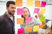 Photo editors looking at multi colored sticky notes on glass in meeting room at creative office poster