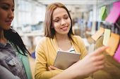Smiling photo editor with female coworker looking at sticky notes in meeting room poster