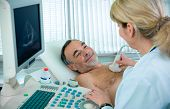 stock photo of ultrasound machine  - Doctor is using ultrasound machine to scan the heart of a senior male patient - JPG