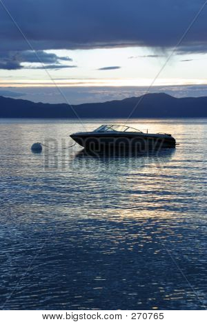 Picture or Photo of A ski boat floats in the calm waters of a mountain lake as the sun rises in the distance.