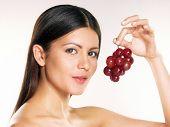 Постер, плакат: Молодая женщина держащая Свежий виноград на белом фоне