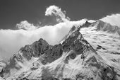 Black And White View From Ski Slope On Snowy Glacier And Mountain Peaks In Clouds. Caucasus Mountain poster