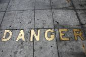 Metal Words in the Sidewalk. Old Metal Words imbedded in cement. The word DANGER written in Brass Le poster