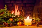 Branches Of A Christmas Tree, Decorations, A Candle On A Wooden Table In Front Of The Fireplace. New poster