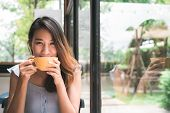 Cheerful Asian Young Woman Drinking Warm Coffee Or Tea Enjoying It While Sitting In Cafe. Attractive poster