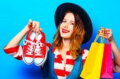 Portrait Of Young Smiling Red-haired White European Woman In Hat And Red Striped Shirt With Gumshoes poster