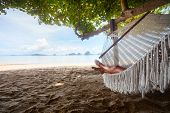 Young lady relaxing in the hammock on the sandy beach with tropical islands on the horizon poster