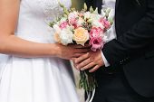 Wedding Bouquet In Couples Hands Outside. Flowers poster
