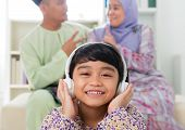 stock photo of malay  - Muslim girl listening to song at home - JPG