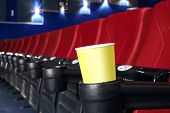 stock photo of cinema auditorium  - Yellow cup for popcorn is stand at red seat in auditorium in cinema theater - JPG