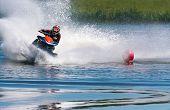 stock photo of ski boat  - Man on jet ski turns left with much splashes - JPG
