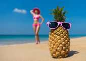 picture of idealistic  - Cheerful pineapple glasses and a woman in a bikini sunbathing on the beach on sea background - JPG