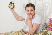 Young Pregnant Woman With Alarm Clock.