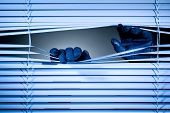 stock photo of snoopy  - Two hands of a thief or a stalker opening closed window shutters at night - JPG