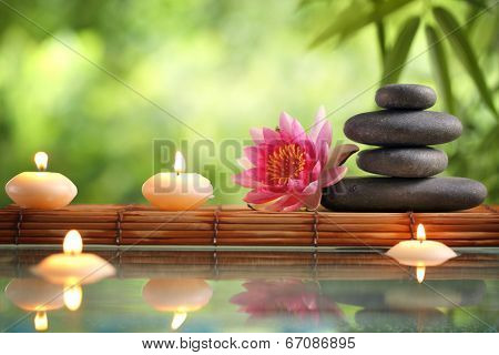 Spa still life with burning candles,zen stone and bamboo mat reflected in a serenity pool poster
