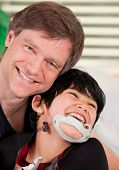 picture of babysitting  - Handsome father holding disabled seven year old son smiling together - JPG