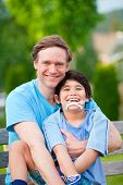 stock photo of babysitting  - Handsome father sitting with smiling disabled seven year old son outdoors - JPG