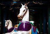 stock photo of carousel horse  - Two white carousel horses under light in a dark promenade - JPG