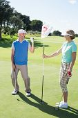 image of ladies golf  - Lady golfer holding eighteenth hole flag for cheering partner on a sunny day at the golf course - JPG
