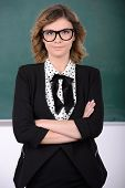 stock photo of character traits  - Smiling teacher standing in front of blackboard - JPG