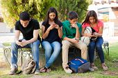 image of ignorant  - Group of teenage boys and girls ignoring each other while using their cell phones at school - JPG