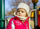 stock photo of playground  - Cute little girl dressed in pink jumpers on child playground october sunny day - JPG