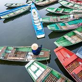 stock photo of conic  - Vietnamese woman with conical hat sitting in a traditional boat on the river - JPG