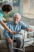 image of nursing  - Disabled man using walking frame and helpful nurse - JPG