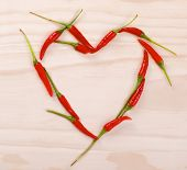 picture of red hot chilli peppers  - Red heart made of red hot chilli peppers on a wooden background - JPG
