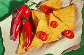 stock photo of nachos  - Tasty nachos and chili pepper on paper - JPG