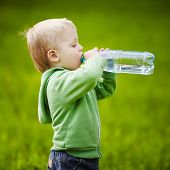 stock photo of little boys only  - little boy drinks mineral water in park