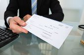 foto of paycheck  - Midsection of businessman giving cheque at desk in office - JPG