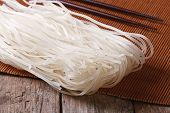 stock photo of chopsticks  - Dry rice noodles with chopsticks close up on the table. horizontal