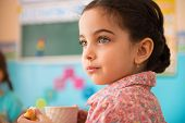 picture of daycare  - Cute little hispanic girl with cup of milk at daycare
