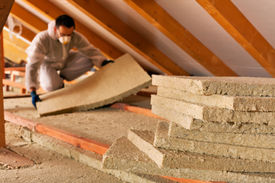 picture of thermal  - Man installing thermal insulation layer under the roof  - JPG