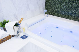 stock photo of champagne color  - Champagne glass and Jacuzzi Spa with colourful light whirlpool - JPG