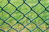 foto of chain link fence  - chain link fence with green grass background - JPG