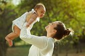 stock photo of baby diapers  - Beautiful woman lifts high her adorable baby up mid air and looks at her smiling - JPG