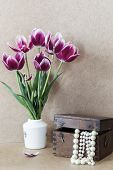 stock photo of mother-of-pearl  - Bright purple flowers in a white vase tulips and wooden chest with pearls - JPG